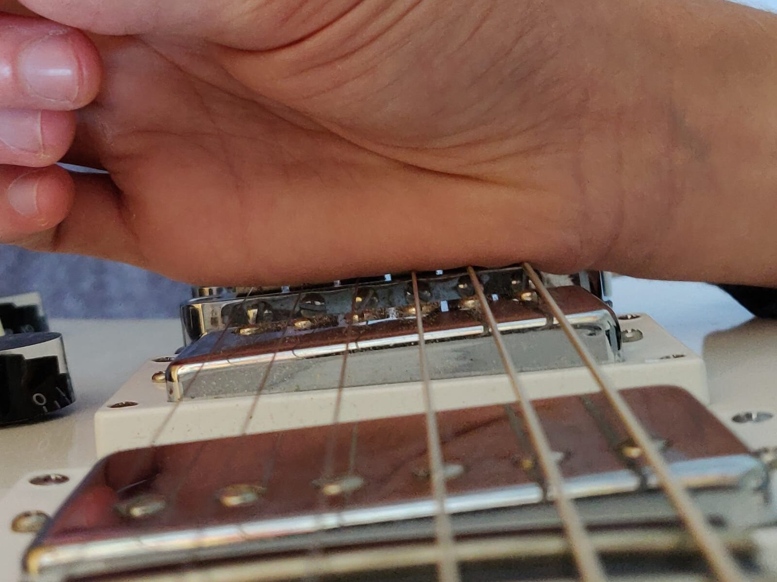 Where to rest your picking hand and palm mute the strings for tidy and clean playing.